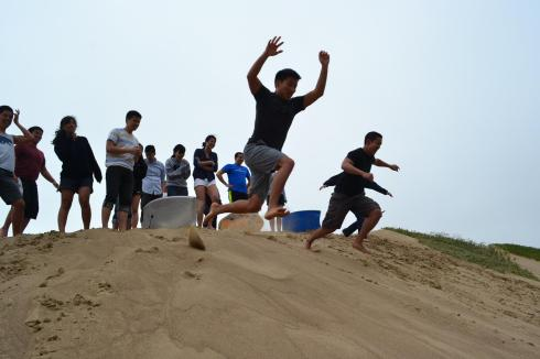 Relay race down and back up the sand dunes